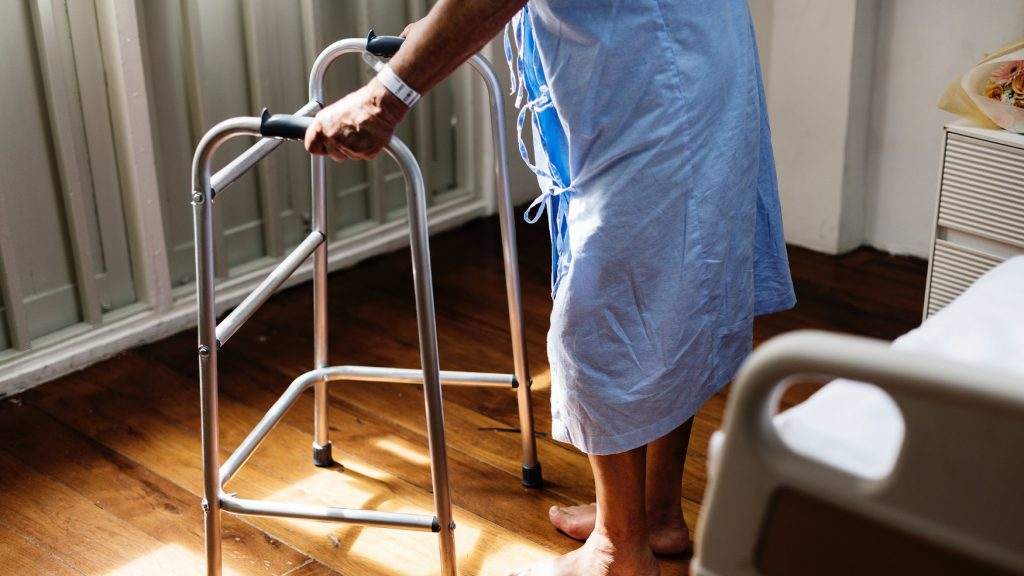 person using walker in hospital gown